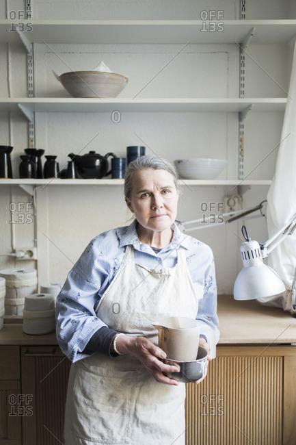 Portrait of senior female potter standing with pitcher against shelves at workshop