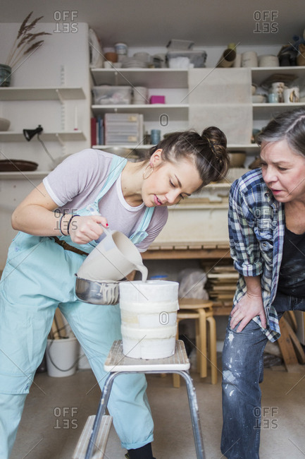 Mature female potter bending while looking at young employee pouring clay from pitcher in vase at workshop