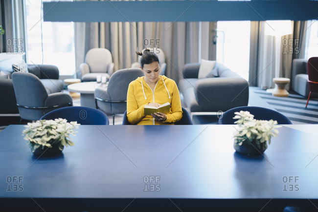 Mid adult businesswoman reading book in office lobby