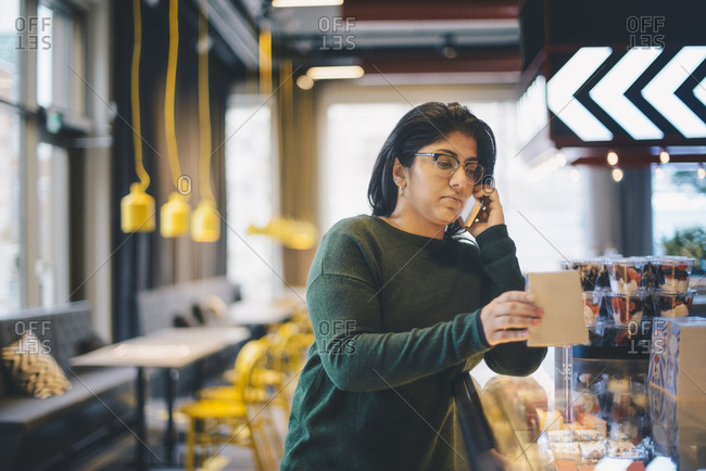 Businesswoman using smart phone while standing in cafeteria at office