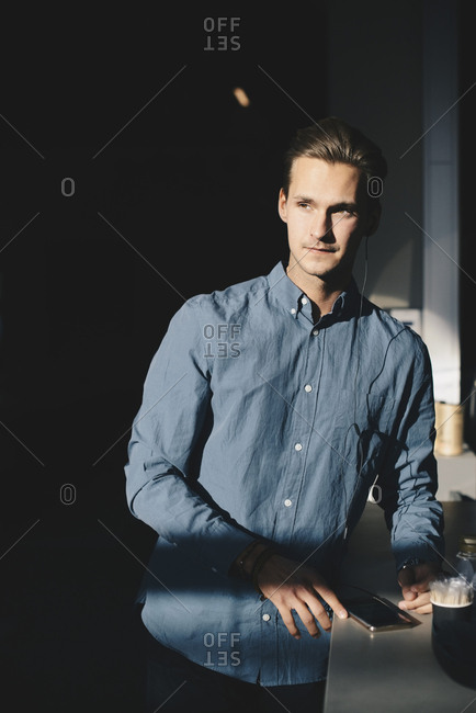 Thoughtful businessman standing with smart phone at table in brightly lit office
