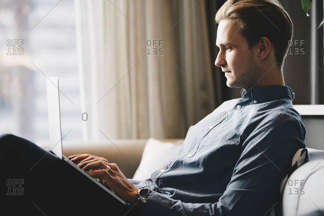 Side view of businessman using laptop at brightly lit office lobby
