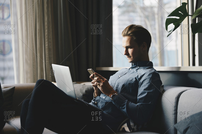 Businessman using smart phone while sitting with laptop at brightly lit office lobby