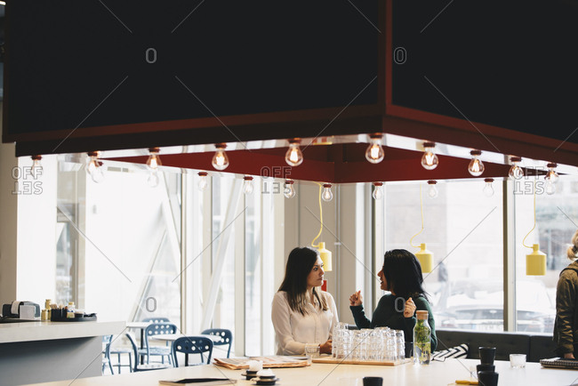 Businesswomen discussing at table in brightly lit office
