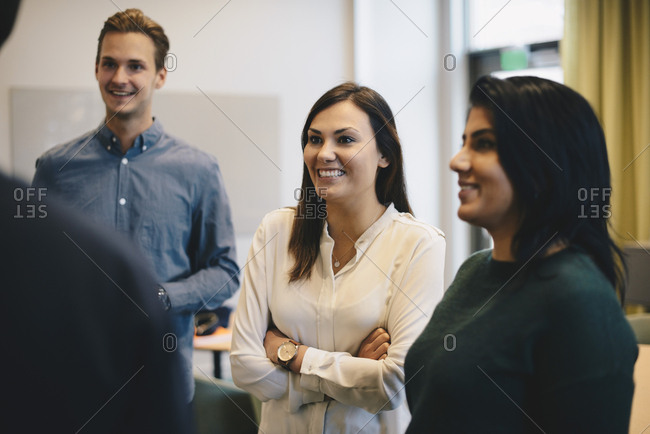 Happy business people discussing with male colleague in board room