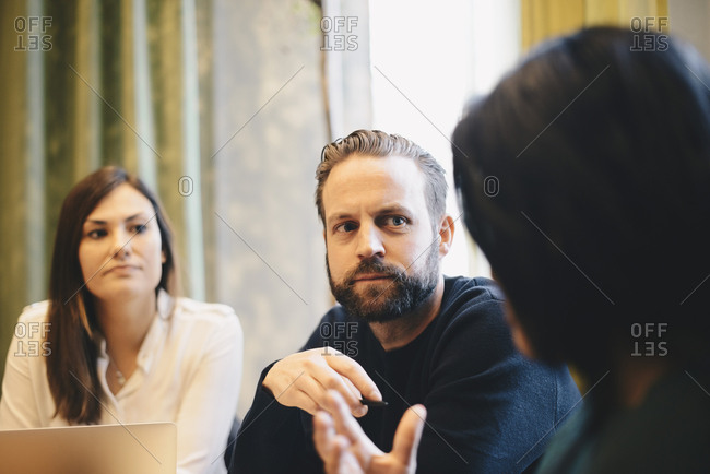 Confident businessman looking at female colleagues during board room meeting