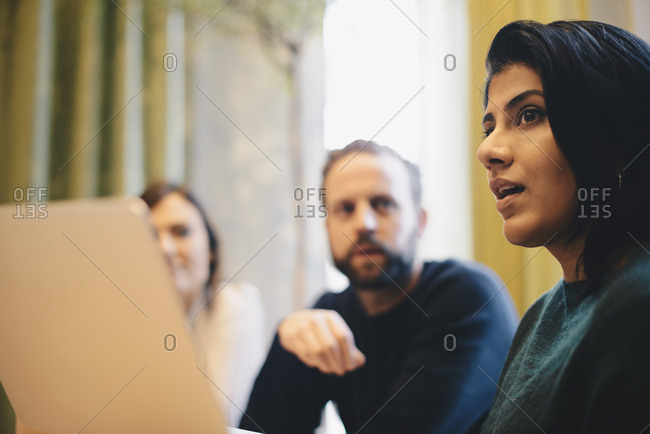 Confident businesswoman explaining strategy during meeting with colleagues in board room