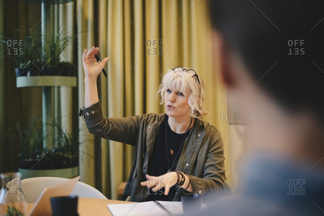 Confident businesswoman explaining strategy while sitting at conference table