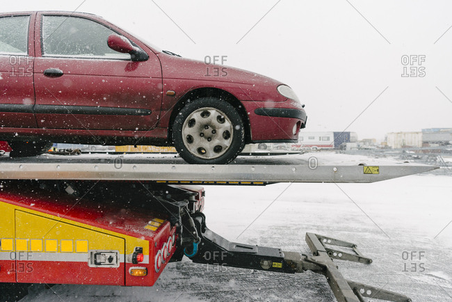 Damaged maroon car on tow truck against sky during winter