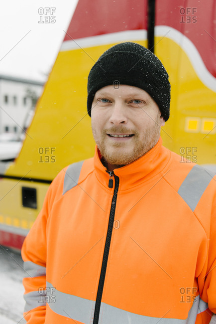 Portrait of smiling male driver standing against tow truck