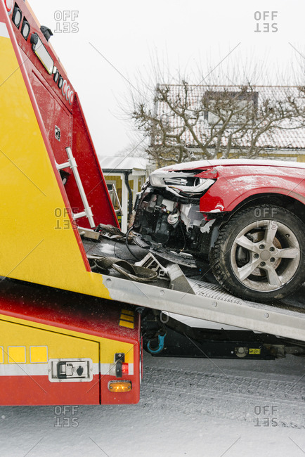 Damaged car on tow truck during winter