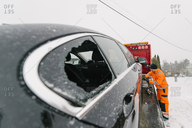 Driver attaching damaged car with tow truck against sky