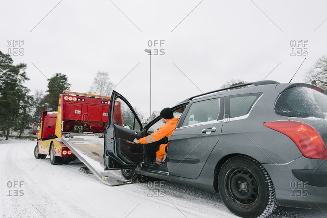 Male driver sitting in car by tow truck on road against sky during winter