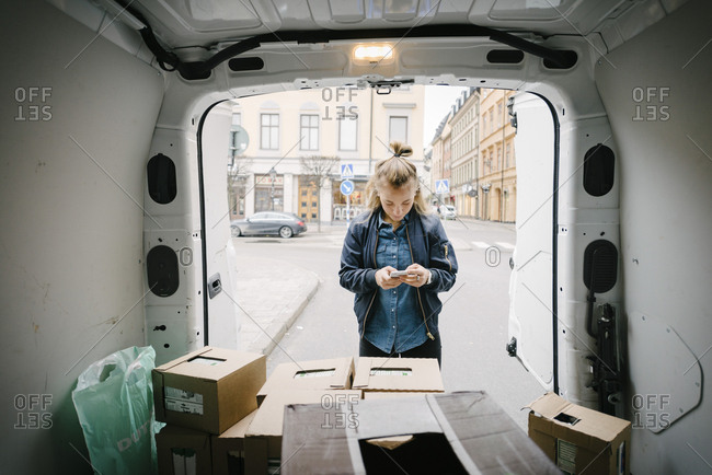 Female worker using mobile phone with cardboard boxes in delivery van