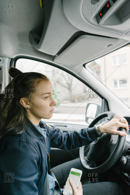 Side view of female worker driving with mobile phone in delivery van