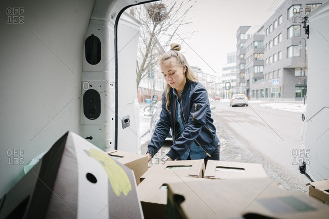 Female worker removing cardboard box from delivery van