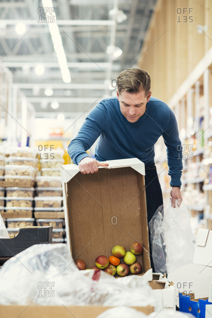 Male owner putting apples from cardboard box in plastic at supermarket