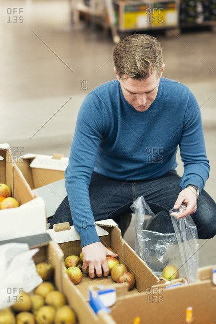 High angle view of owner putting apples in plastic bag from cardboard box at supermarket