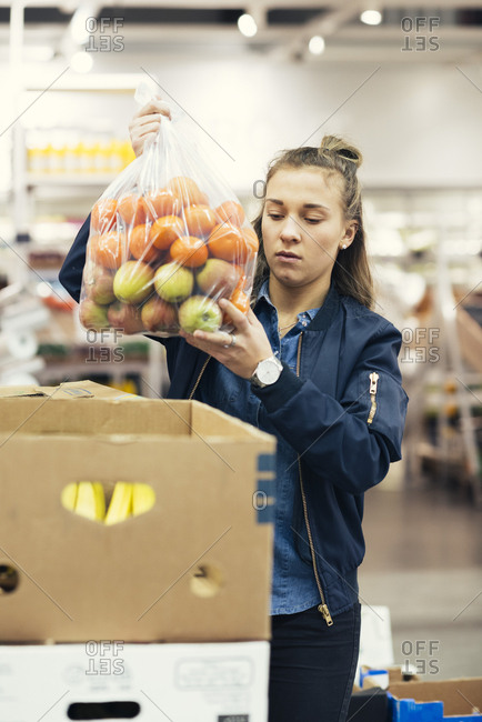 Young female worker holding plastic bag with oranges and apples over cardboard box at supermarket
