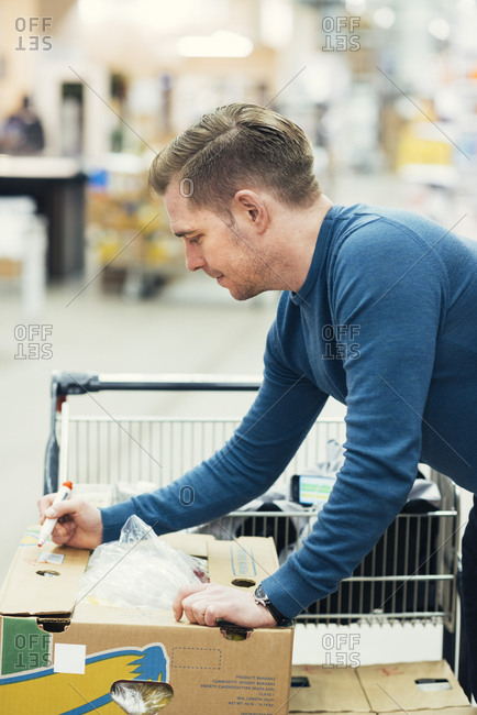 Side view of owner writing with felt tip pen on cardboard box at supermarket