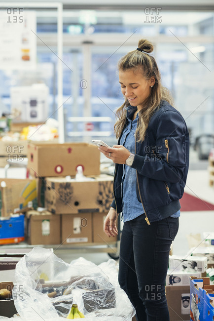Young female worker using mobile phone while standing amidst cardboard boxes at supermarket
