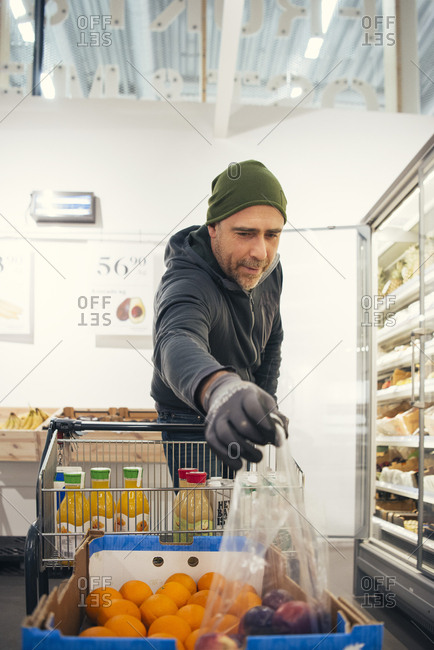 Male worker picking plastic bag with apples from cardboard box at supermarket
