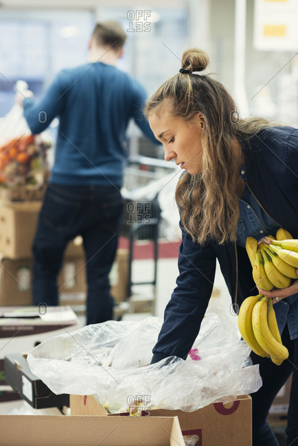 Young female worker removing bananas from cardboard box with owner in background