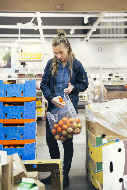 Young female worker holding plastic bag with oranges and apples while standing amidst cardboard boxes at supermarket