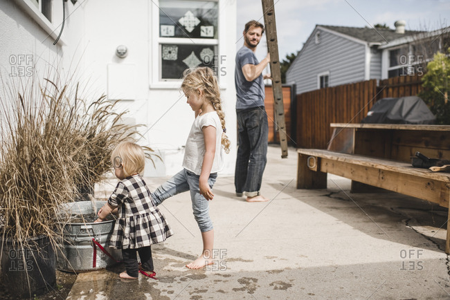 Father carrying ladder while looking at daughters playing with water outside house