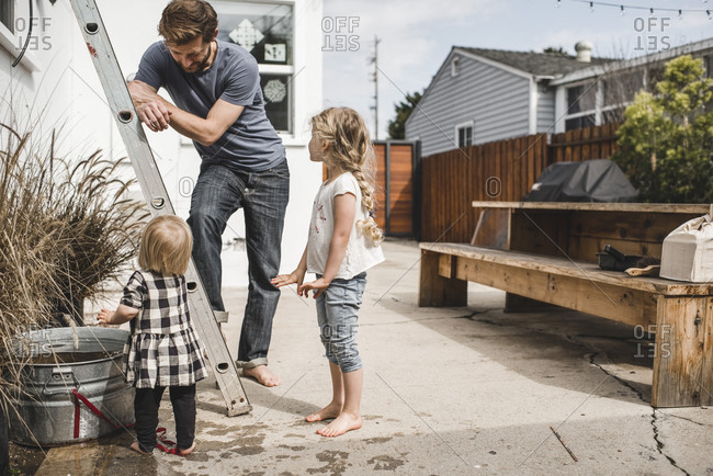 Father looking at daughters playing with water outside house