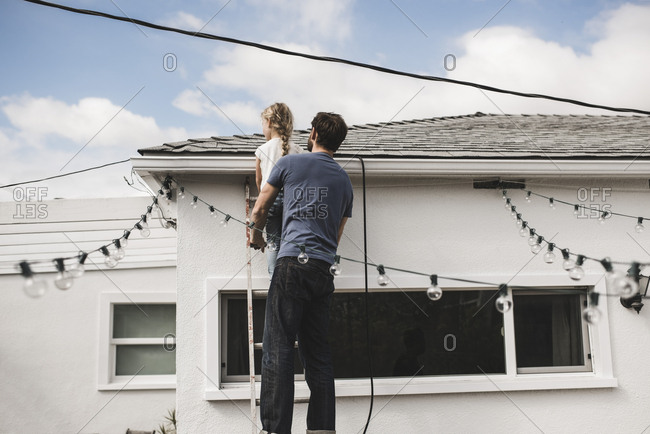 Rear view of man with daughter climbing up ladder at house
