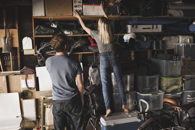 Rear view of man looking at woman arranging boxes on shelf in storage room