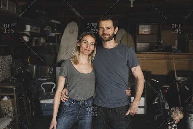 Portrait of loving parents standing by daughter at storage room