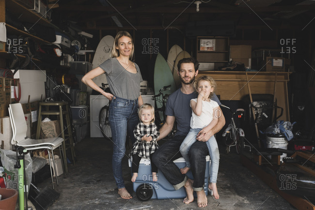 Portrait of parents and children in storage room of house