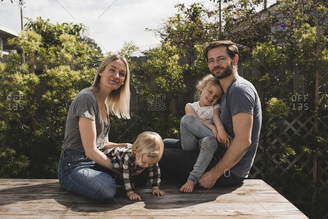 Portrait of parents and children sitting on floorboard in yard