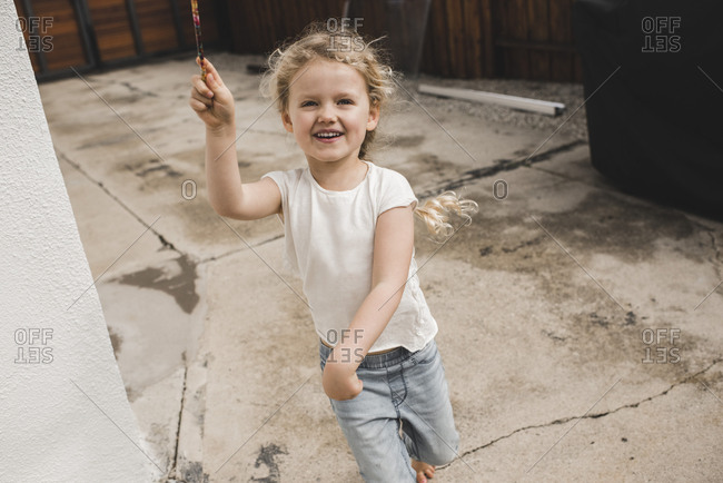 Portrait of happy girl playing with magic wand outside house