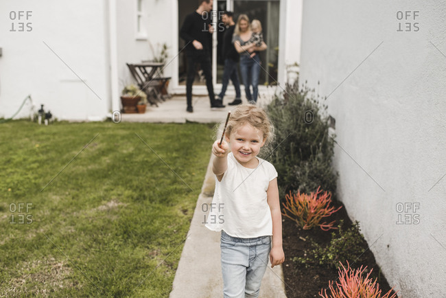 Portrait of girl showing magic wand with family in background at yard