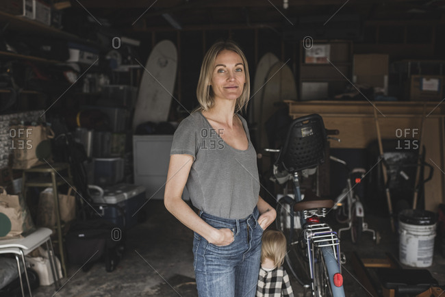 Portrait of mid adult woman standing with hands in pockets by daughter at storage room