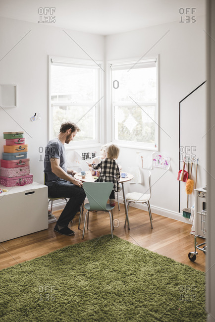 Father playing with daughter at small dining table in playroom