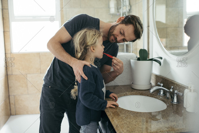 Mid adult father brushing daughter's teeth at sink in bathroom