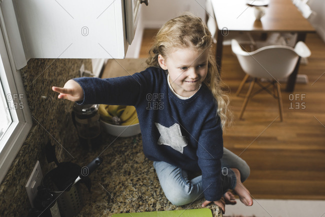 High angle view of girl pointing while sitting on kitchen counter at home