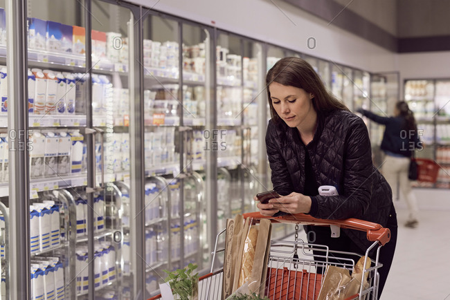 Woman text messaging while leaning on shopping cart at refrigerated section in supermarket