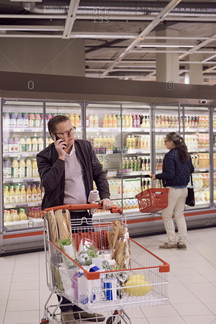 Mature man talking on mobile phone while woman looking at display cabinet in refrigerated section of supermarket