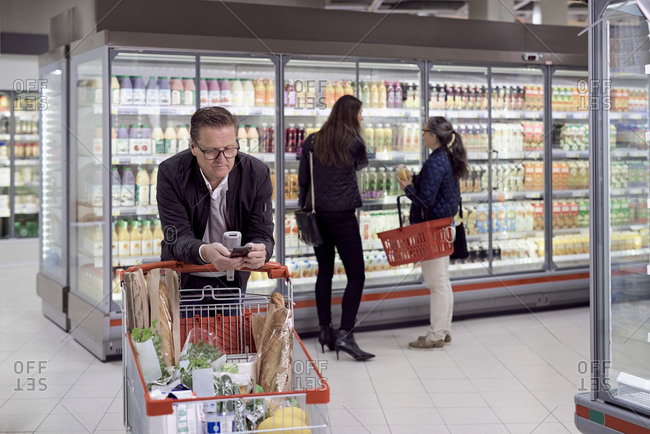 Mature man using mobile phone while leaning on shopping cart against women buying juices at refrigerated section in super