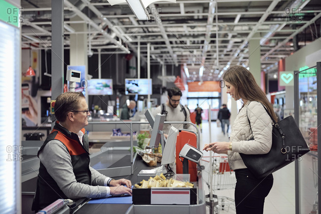 Mature cashier looking at woman paying through technology at checkout counter in supermarket