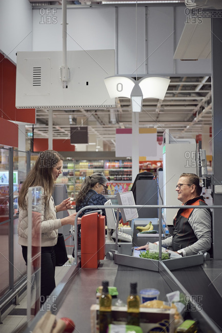 Woman talking to mature cashier while paying at checkout counter in supermarket