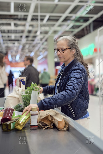 Mature woman standing with groceries and bag at checkout counter in supermarket