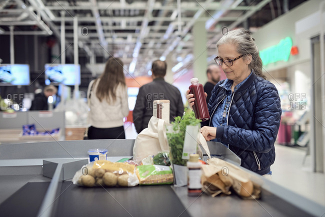 Mature woman keeping juice bottle in bag while standing at checkout counter
