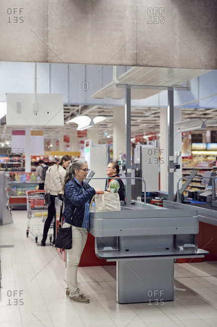 Woman with shopping bag standing by checkout counter at supermarket