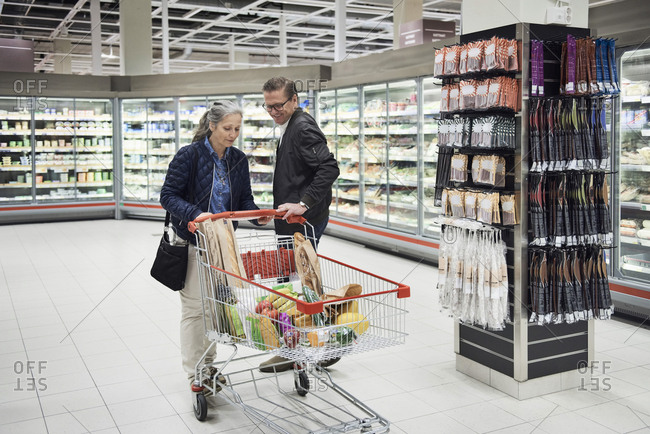 Mature couple with groceries in shopping cart at refrigerated section of supermarket